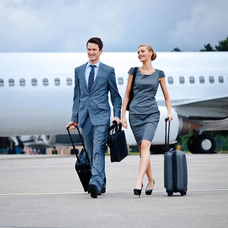 A man and woman in business attire walk with luggage away from a private jet