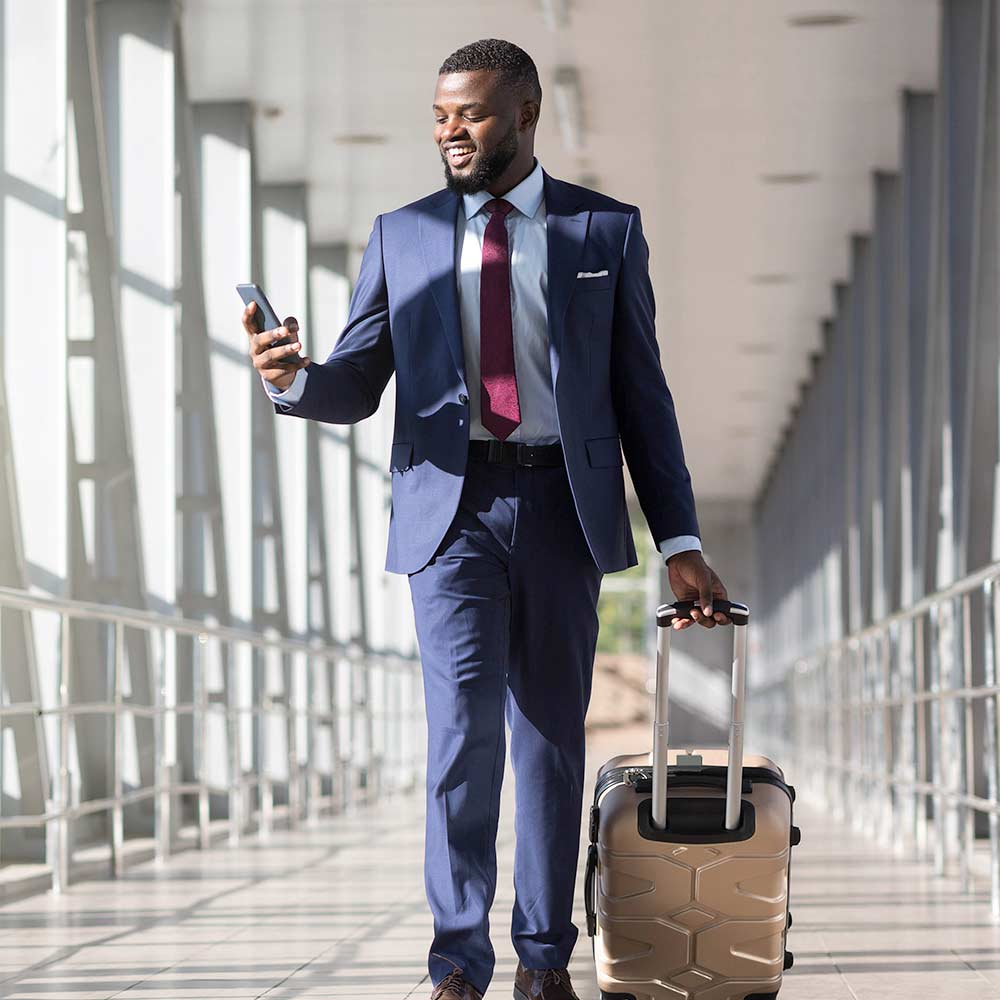 A young business man walks through an airport looking at his phone