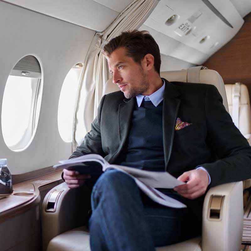 A man looks out the window of a private jet