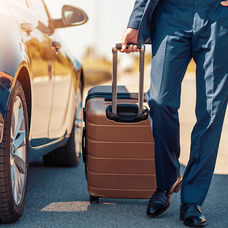 A business man exits a nice car with luggage in tow