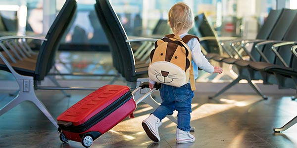 A child walks through an airport with a bag in tow