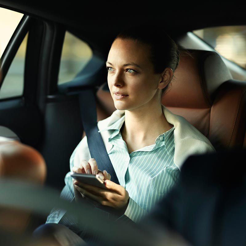 Woman in backseat of car using phone