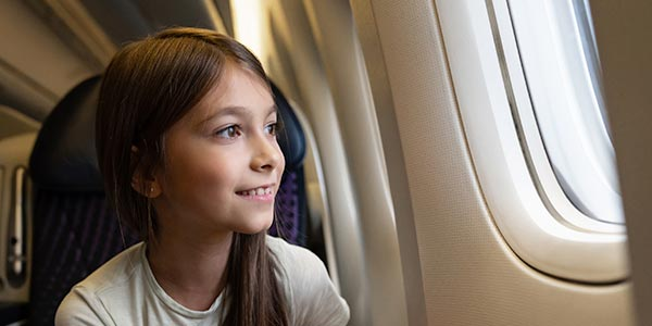 A child looks out of an airplane window