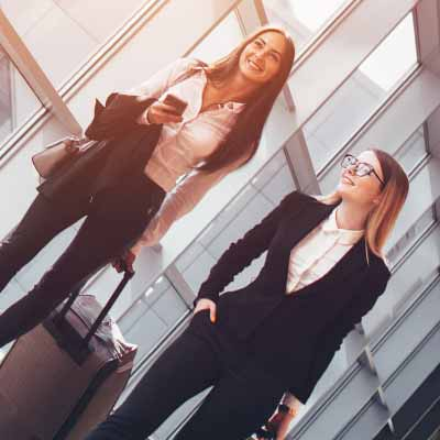 Two business women walk through an airport