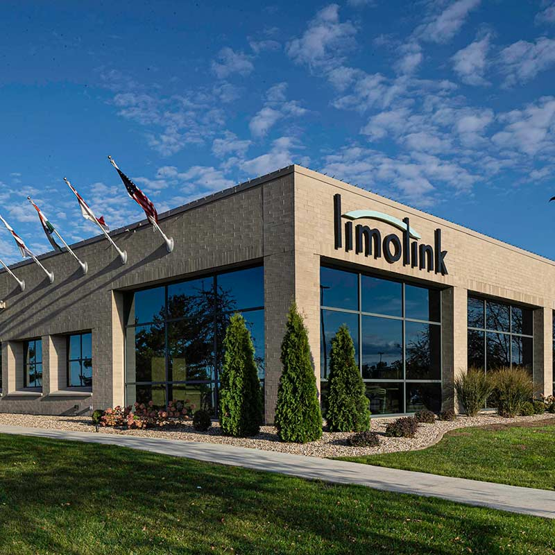 Exterior shot of the LimoLink office building with large logo and flags